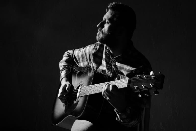 Den ledsna Caucasian manliga musikern som spelar gitarren på etapp, fokuserar förestående svart white arkivbild