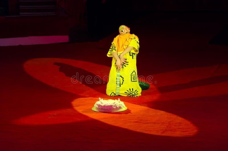 Den ledsna clownen sitter på arenan nära den stora födelsedagkakan med bränningstearinljus arkivbild