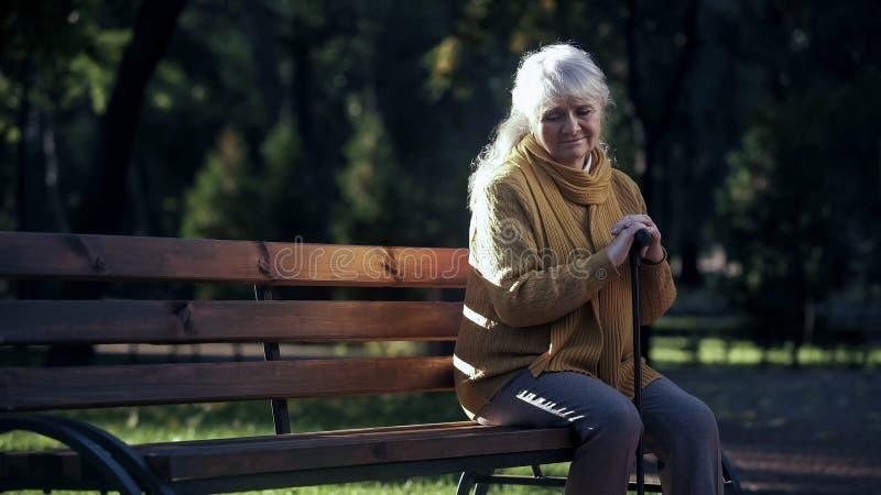 Den ledsna ensamma gamla kvinnan som sitter på bänk parkerar in, övergett äldre folk bara royaltyfria foton