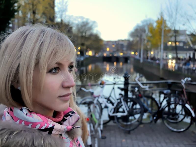 Den ledsna flickan i rosa färger klår upp nära kanalen av Amsterdam på blå timmeafton bland cyklar arkivbild