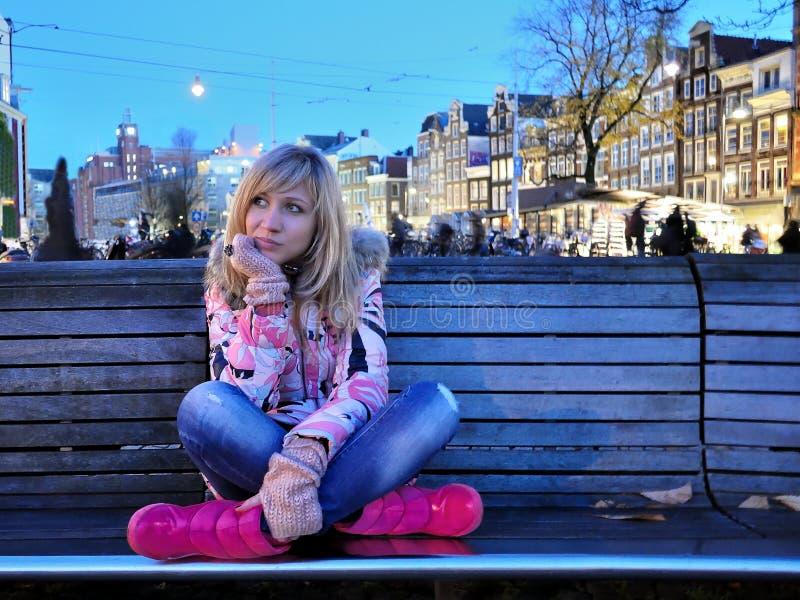Den ledsna flickan i rosa färger klår upp nära kanalen av Amsterdam på blå timmeafton bland cyklar royaltyfria bilder