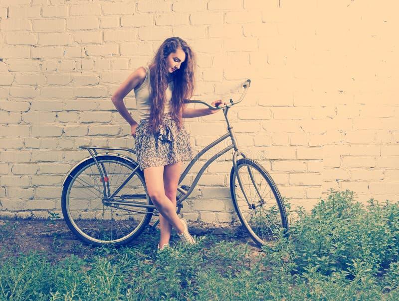 Den ledsna flickan med hennes stads- cykel som står den near vita väggen och ner ser på fot, retro seende instagram, tonade skott arkivfoto