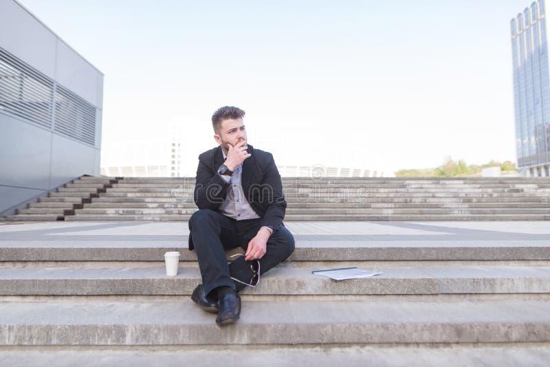 Den ledsna fundersamma affärsmannen sitter på momenten och blickarna till sidan arkivbild