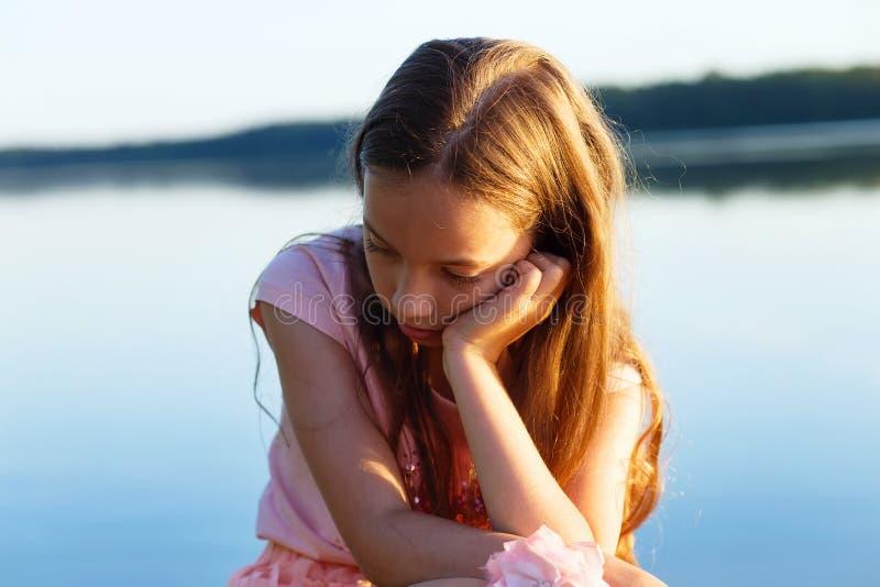 Den ledsna härliga tonåriga flickan ser med den allvarliga framsidan på sjösidan royaltyfri fotografi