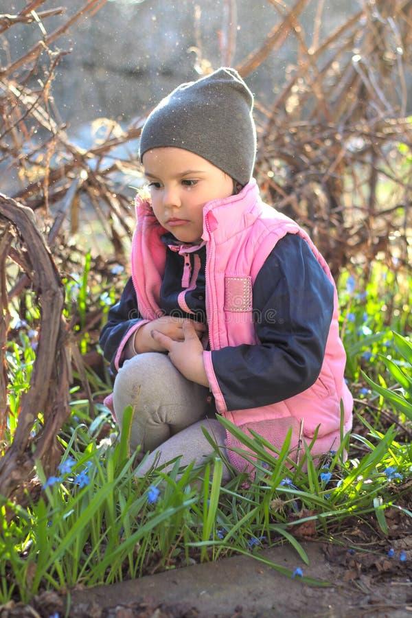 den ledsna, kränkta, klädda flickan i ett lock sitter varmt på hennes knä bland blommorna av blåa snödroppar i vingården royaltyfri bild