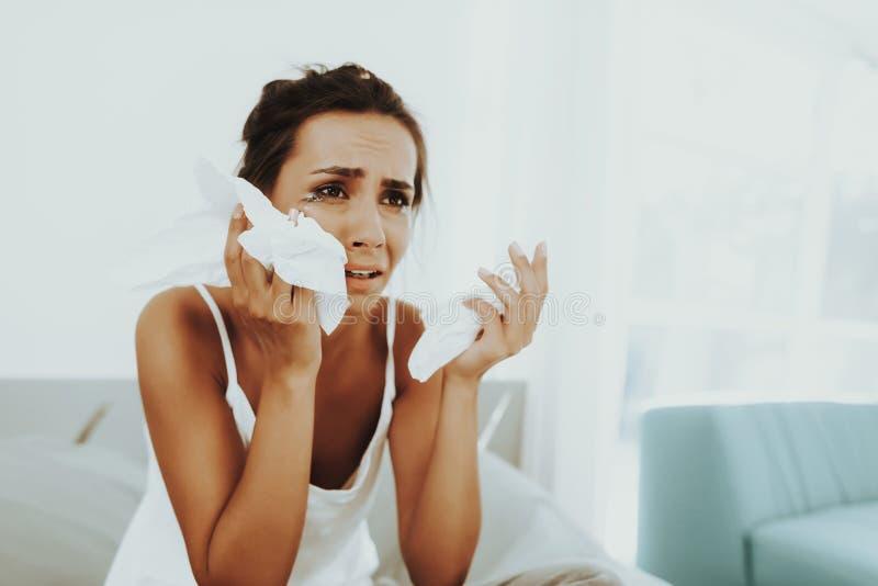 Den ledsna kvinnan med flödad mascara torkar revorna arkivbild