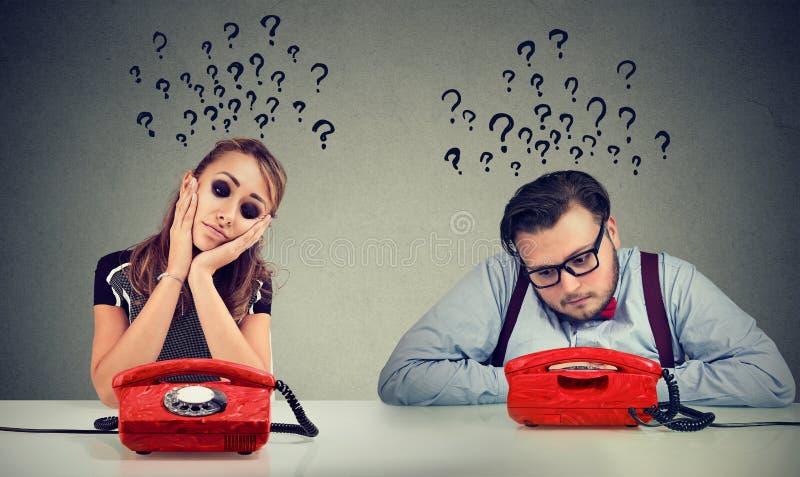 Den ledsna mannen och kvinnan som väntar på en påringning från de, har många frågor arkivbilder