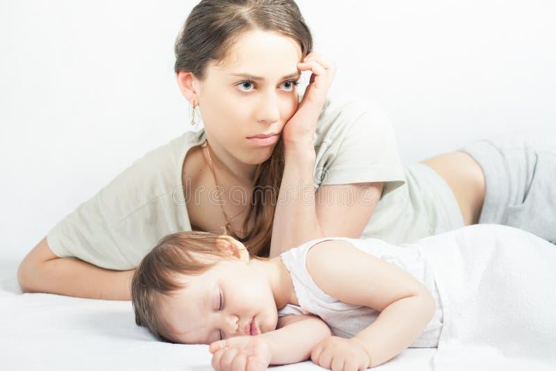 Den ledsna modern med behandla som ett barn Deprimerad kvinna som sover barnet fotografering för bildbyråer