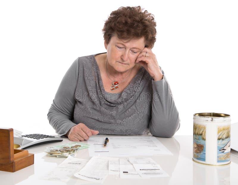 Den ledsna pensionärkvinnan har pengarproblem - armod i åldern arkivfoto