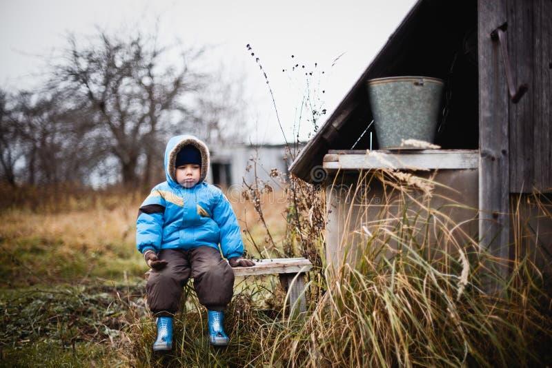 Den ledsna pysen i ett blått omslag och en brunt flåsar sammanträde på bänken Bredvid trästrukturen Dyster dag i byn royaltyfri fotografi