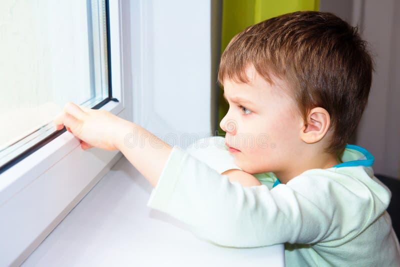Den ledsna pysen ser ut fönstret Stående av den Caucasian pojken nära fönster Melankoliskt barn fotografering för bildbyråer