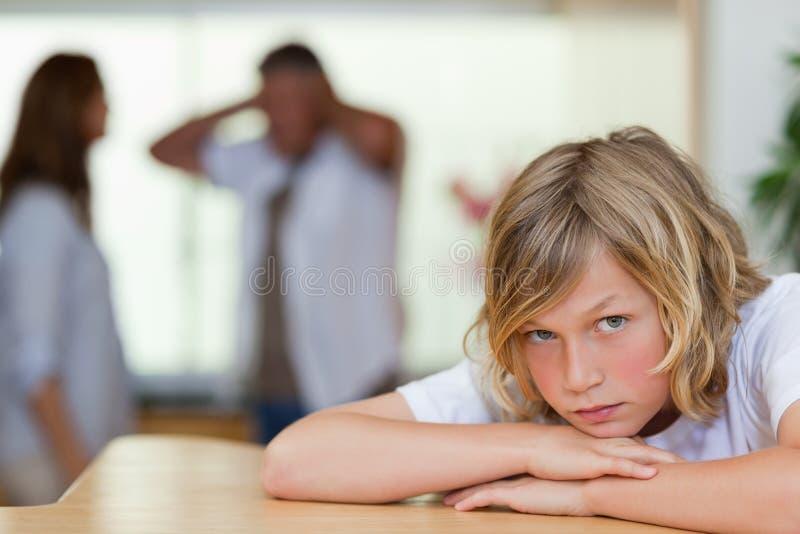 Den ledsna seende pojken med att argumentera uppfostrar bak honom arkivbild