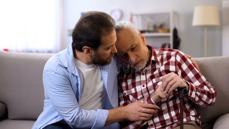 Den ledsna sonen som lugnar den rörelsehindrade höga fadern, hälsoproblem, att lida som är starkt, smärtar arkivfoton