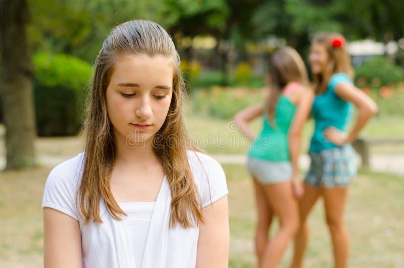Den ledsna tonårs- flickan som kasseras av andra tonårs- flickor parkerar in arkivfoto