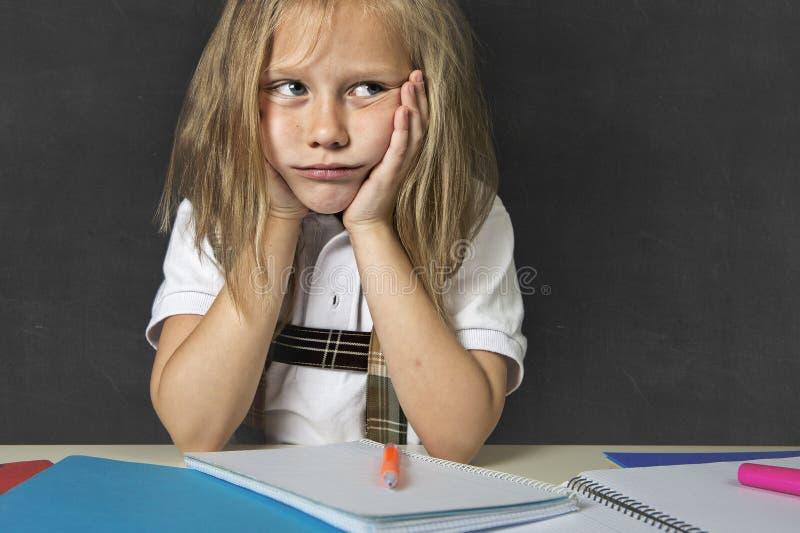 Den ledsna trötta gulliga blonda yngre skolflickan i spänningen som arbetar göra läxa, borrade förkrossat fotografering för bildbyråer