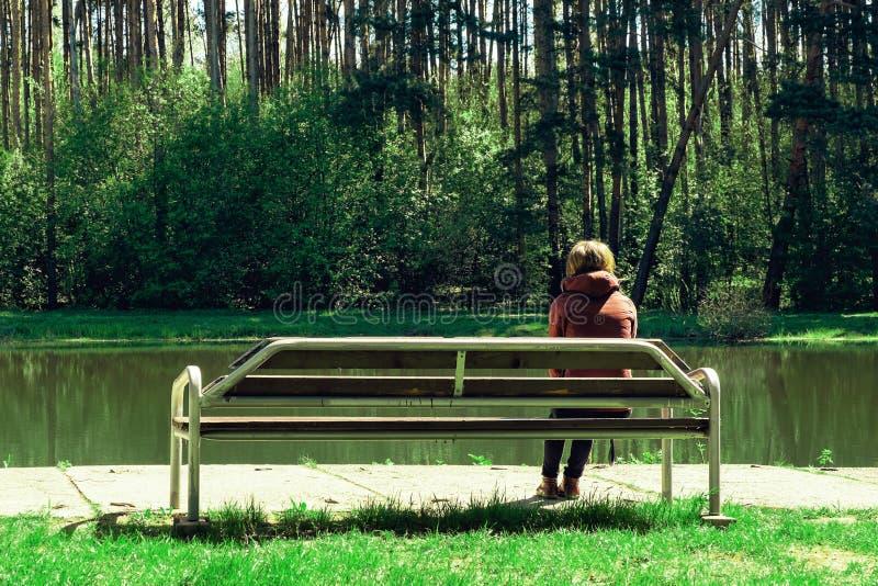 Den ledsna unga flickan och sitter på en träbänk i parkera, henne sveks av den söta förälskelsen Drömmar av framtiden arkivbild