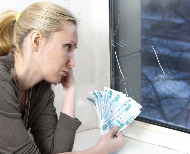 Den ledsna unga kvinnan räknar pengar för fönsterreparation med bristningen, brutet exponeringsglas royaltyfria foton