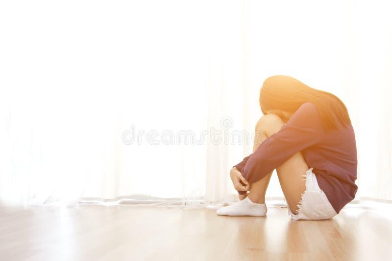 Den ledsna unga kvinnan sitter i hennes rum och beläggning fotografering för bildbyråer