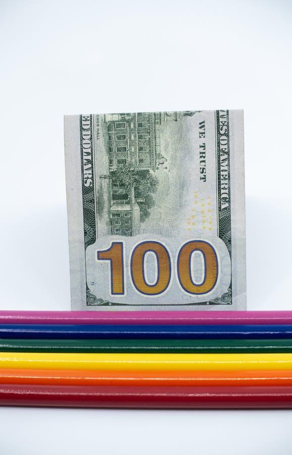 Den LGBT- och Gay Pride regnbågen färgade blyertspennor med en räkning $100 mot en vit bakgrund Jämställdhet- och mångfaldbegrepp royaltyfria foton