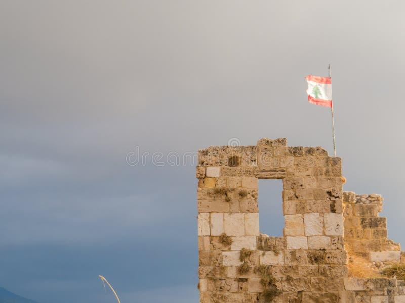 Den libanesiska flaggan på fördärvar i Byblos, Libanon royaltyfria bilder