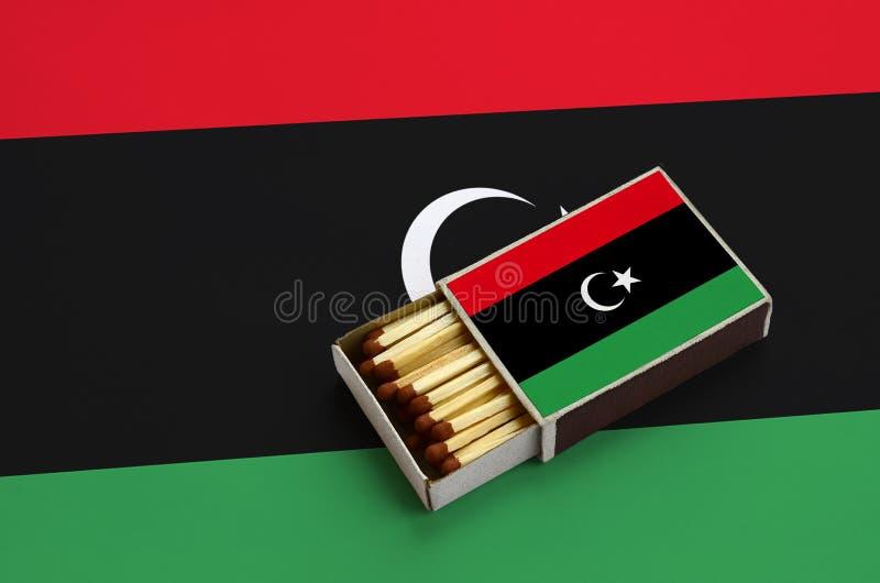 Den Libyen flaggan visas i en öppen tändsticksask, som fylls med matcher och ligger på en stor flagga arkivfoto