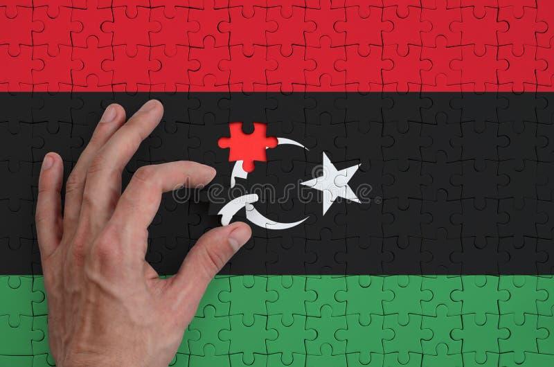 Den Libyen flaggan visas på ett pussel, som handen för man` s avslutar för att vika fotografering för bildbyråer