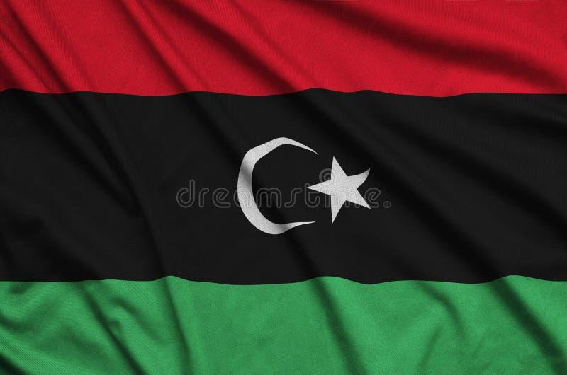 Den Libyen flaggan visas på ett sporttorkduketyg med många veck Baner för sportlag royaltyfria foton