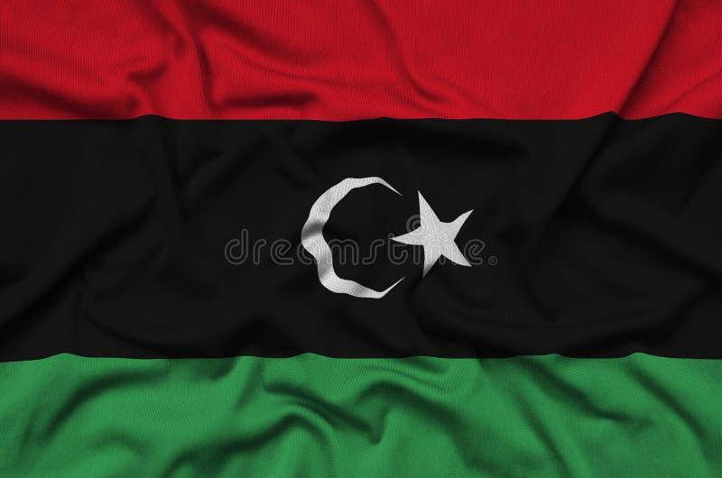 Den Libyen flaggan visas på ett sporttorkduketyg med många veck Baner för sportlag royaltyfri foto