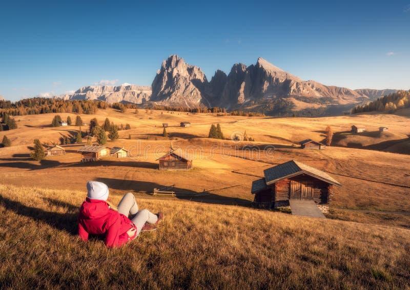 Den liggande kvinnan på kullen ser på ängar och berg arkivbilder