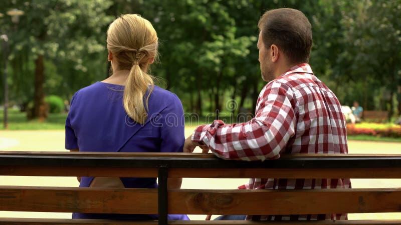 Den likgiltiga mannen och kvinnan som sitter på bänken, inga gemensamma intressen, bryter upp royaltyfri bild