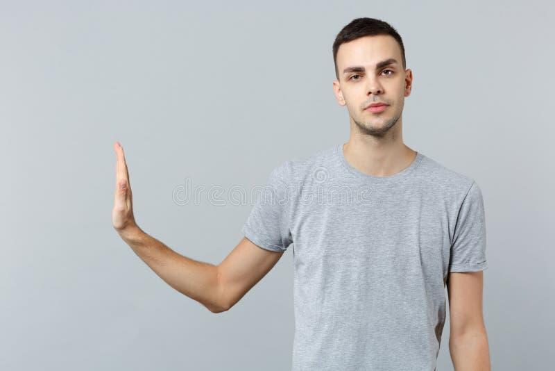 Den likgiltiga unga mannen i tillfällig kläder som ser kameran som visar stoppgest med, gömma i handflatan åt sidan isolerat på d royaltyfria foton