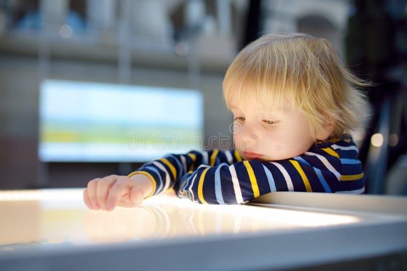 Den lilla сaucasian pojken ser en utläggning i ett vetenskapligt museum royaltyfria bilder