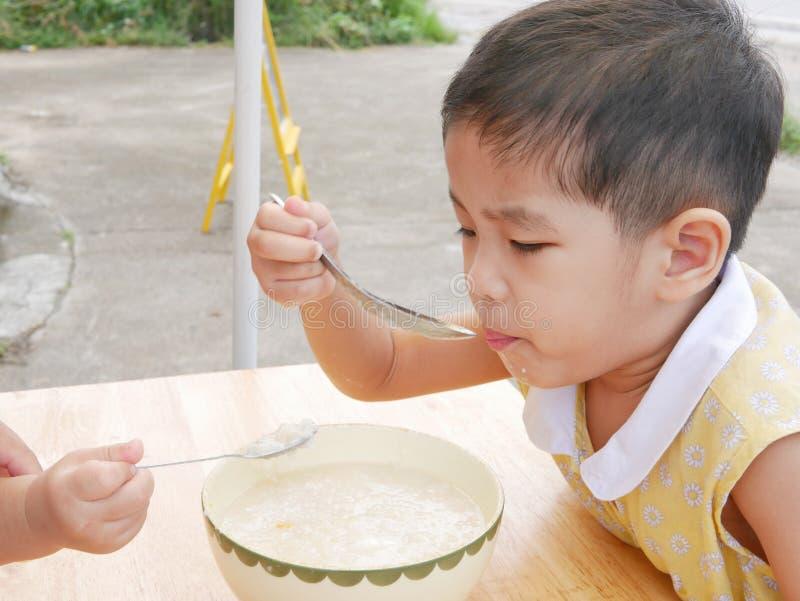 Den lilla asiatet behandla som ett barn flickan som äter varm rishavregröt av henne royaltyfria foton