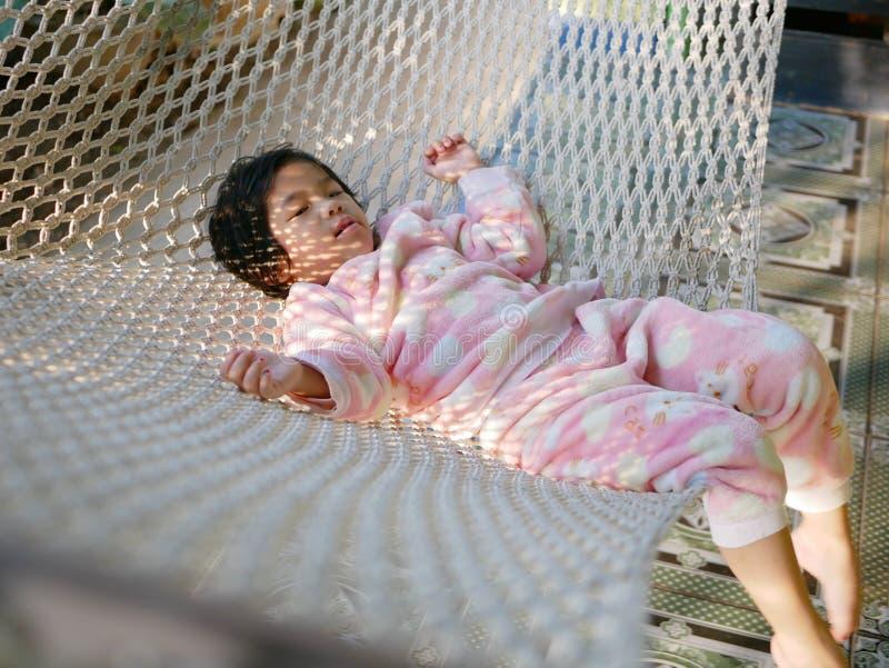 Den lilla asiatet behandla som ett barn flickan som bekvämt ner ligger på en hängmatta med morgonsolljuset royaltyfri bild