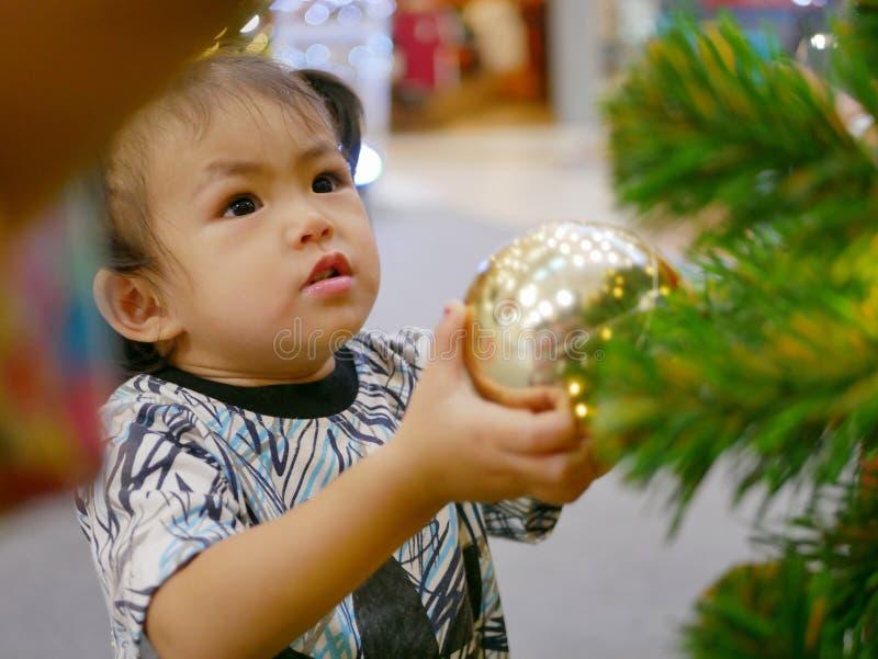 Den lilla asiatet behandla som ett barn flickan som drar en hängande boll på en julgran i en shoppinggalleria royaltyfria foton