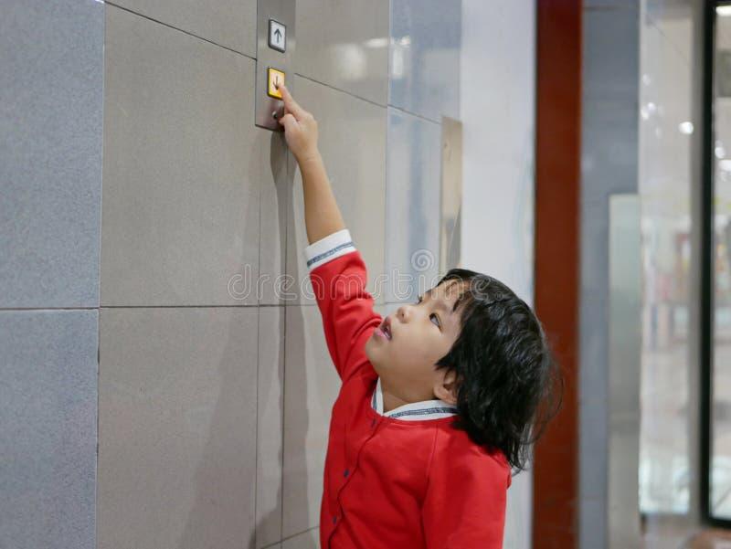 Den lilla asiatet behandla som ett barn flickan, 3 gamla som år ut når hennes hand för att försöka att skjuta hissknappen arkivfoton