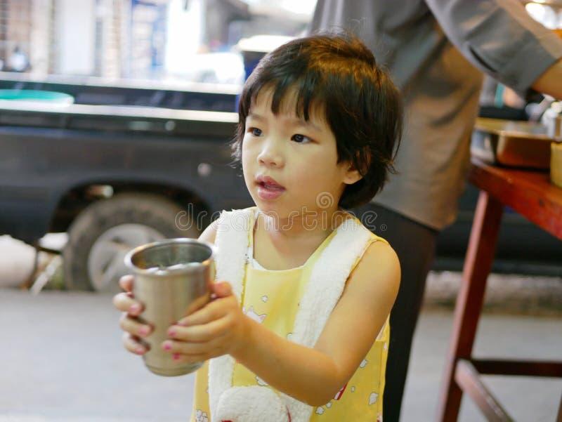 Den lilla asiatet behandla som ett barn flickan som hjälper hennes bärande koppar för liten tant av vatten för att tjäna som andr royaltyfri bild