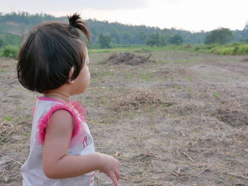Den lilla asiatet behandla som ett barn flickan som långt borta ser på ett öppet fält, som hon kan se och intresserat i saker i e fotografering för bildbyråer