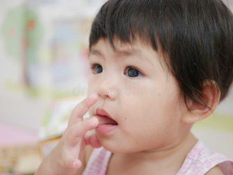 Den lilla asiatet behandla som ett barn flickan som sätter hennes finger in i hennes mun royaltyfri foto
