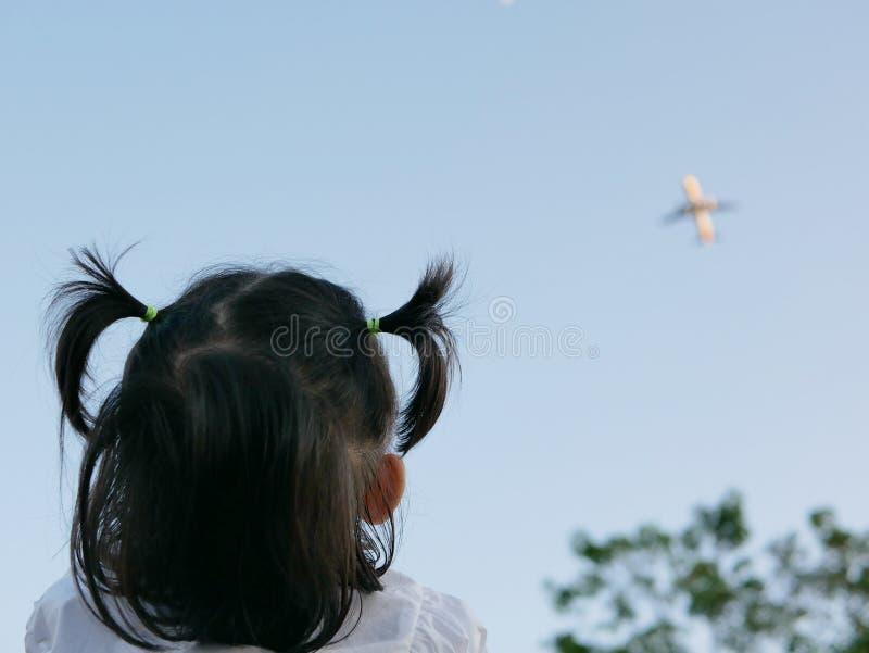 Den lilla asiatet behandla som ett barn flickan som ser ett flygplan som flyger över himlen arkivfoton