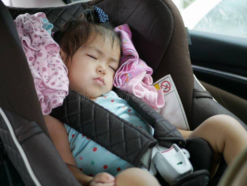 Den lilla asiatet behandla som ett barn flickan som sover på ett bilsäte för, behandla som ett barn säkerhet royaltyfria bilder
