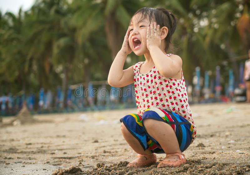Den lilla asiatet behandla som ett barn flickan som spelar sand på stranden arkivbilder