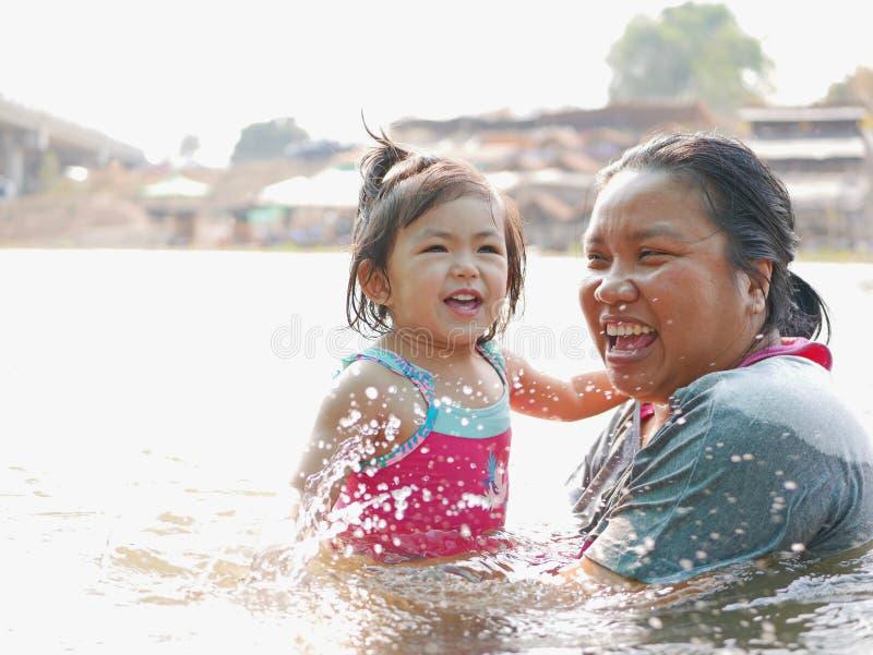 Den lilla asiatet behandla som ett barn flickan tycker om att spela vatten i en flod med hennes liten tant royaltyfri foto