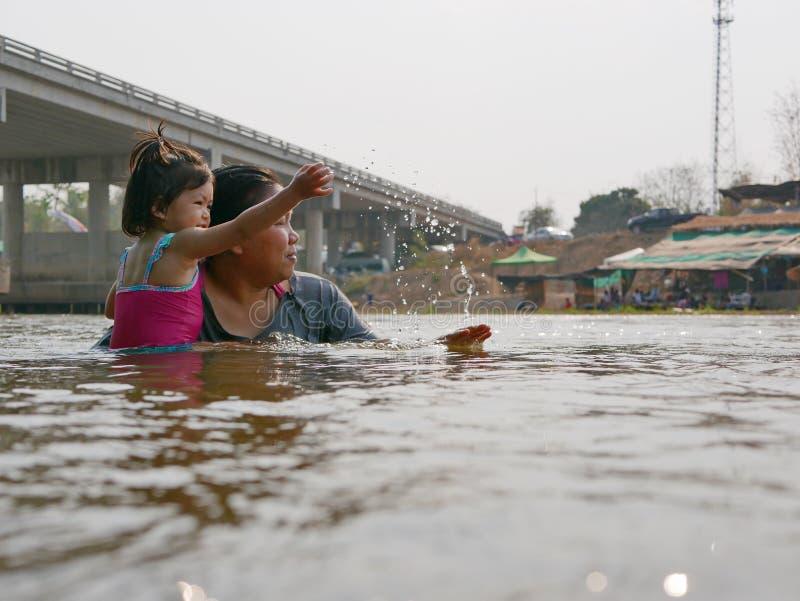 Den lilla asiatet behandla som ett barn flickan tycker om att spela vatten i en flod med hennes liten tant arkivbild