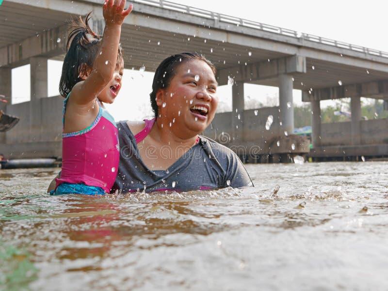 Den lilla asiatet behandla som ett barn flickan tycker om att spela vatten i en flod med hennes liten tant royaltyfri fotografi