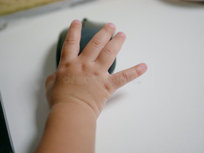 Den lilla asiatet behandla som ett barn handen för ` s på en datormus arkivfoto