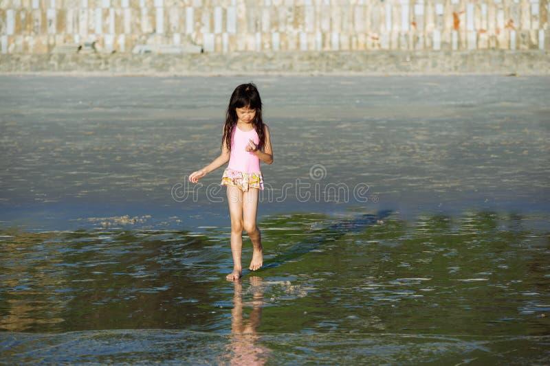 Den lilla asiatiska flickan går från stranden till havet fotografering för bildbyråer