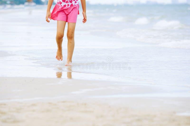 Den lilla asiatiska flickan går på stranden fotografering för bildbyråer