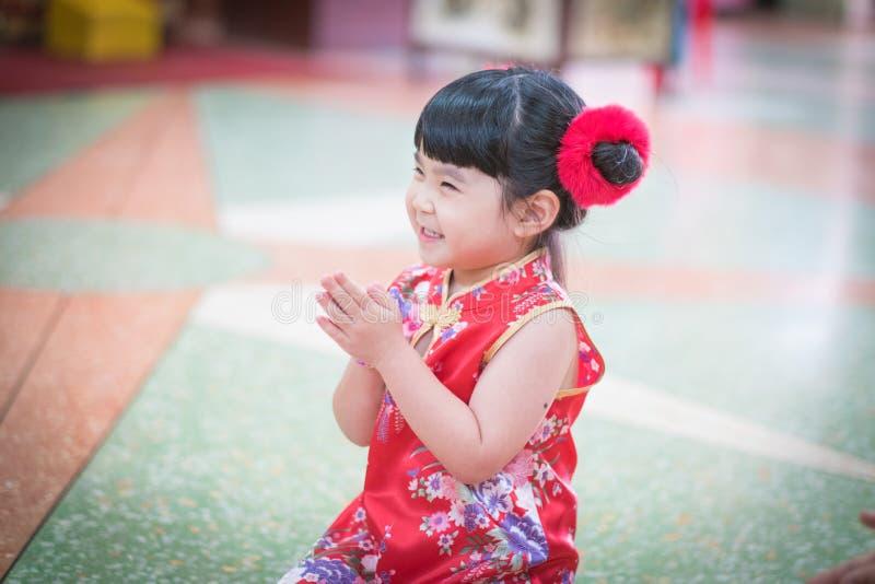 Den lilla asiatiska flickan som önskar dig ett lyckligt kinesiskt nytt år royaltyfri foto