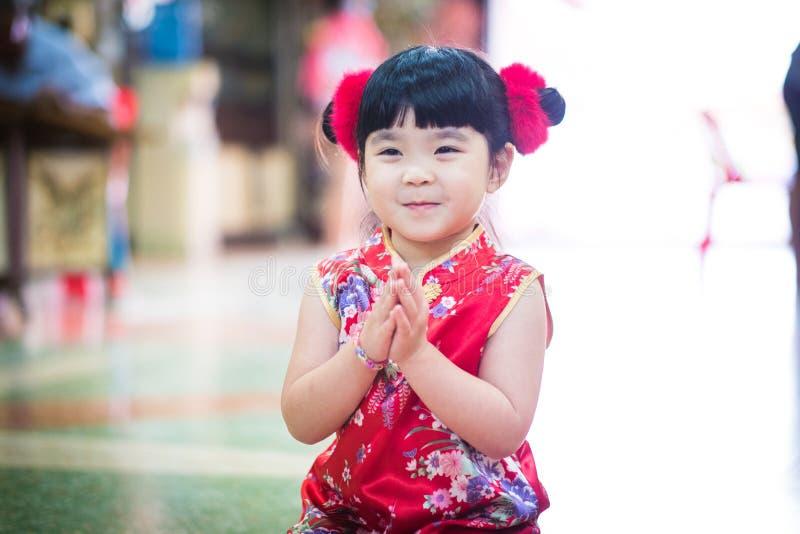 Den lilla asiatiska flickan som önskar dig ett lyckligt kinesiskt nytt år royaltyfria bilder